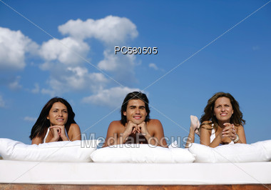 A man and two women lying on cushions Stock Photo