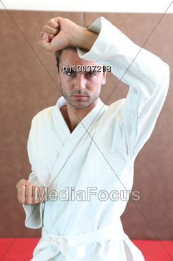 Man Wearing Martial Arts Clothing Stood In Defence Stance Stock Photo