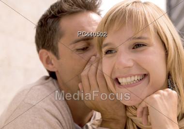 Man Whispering Secret To Woman Stock Photo