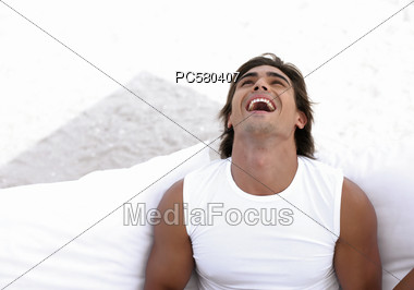 Man In White Muscle Shirt Laughing Outside Stock Photo
