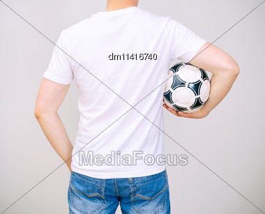 Man In White T-shirt With Ball. Grey Background Stock Photo