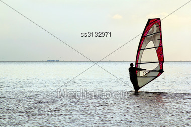 Man Windsurfer On The Water Surface Stock Photo