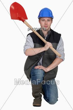 Man With Spade Kneeling Stock Photo