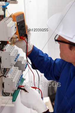 Man With A Voltmeter In Electrical Panel Stock Photo