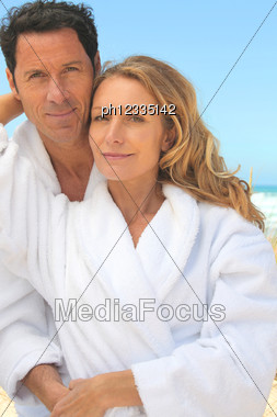 Man And Woman In Toweling Robes On The Beach Stock Photo