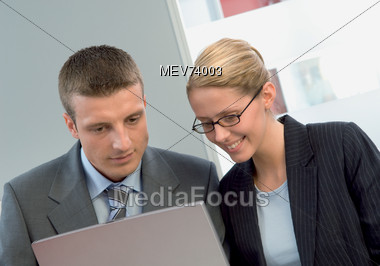 Man & Woman Looking At Portable Laptop Stock Photo