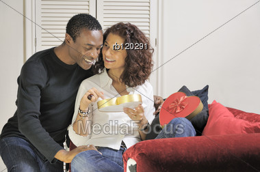 Man And Woman Relax Together With A Heart Shaped Chocolate Box Stock Photo