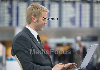 Man Working On Laptop At Airport Stock Photo