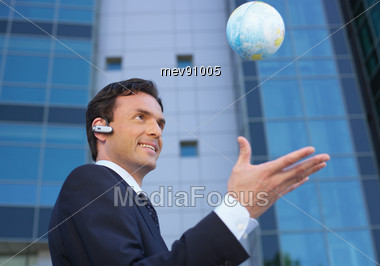 Manager Tossing Up Small Globe Stock Photo