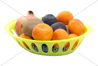 Mandarins, Pomegranate, Plums And Kiwi Fruits In The Green Plate Stock Photo