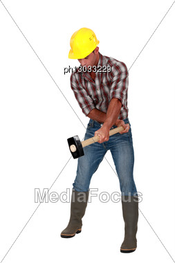 Manual Worker With A Sledgehammer. Stock Photo