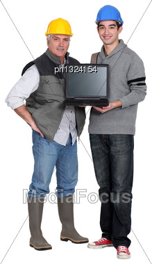 Manual Workers With A Laptop Stock Photo
