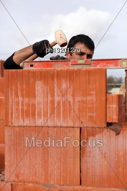 Mason Adjusting Brick Wall Stock Photo