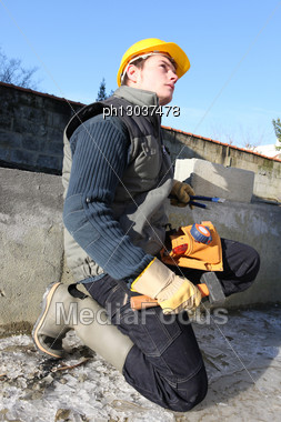 Mason Kneeling By Incomplete Wall Stock Photo