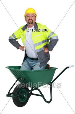 Mason Kneeling In Wheelbarrow Stock Photo