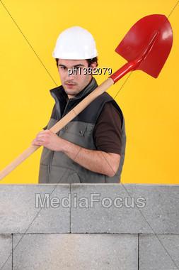 Mason Stood By Unfinished Wall Stock Photo
