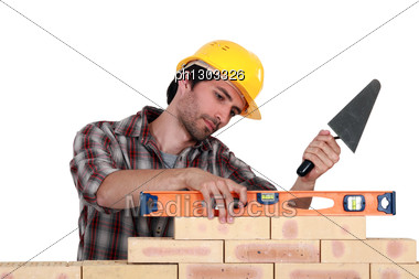Mason Using A Level To Check His Wall. Stock Photo