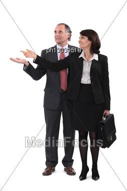 Mature Businesscouple Gesturing At Blank Copyspace Stock Photo