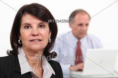 Mature Businesswoman And Man Using A Laptop Stock Photo