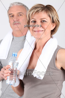 Mature Couple Drinking Water After A Workout Stock Photo