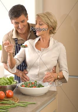 Mature Couple Preparing Salad Stock Photo