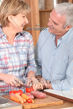 Mature Couple Preparing Vegetables Stock Photo