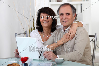 Mature Couple Using A Credit Card Online Stock Photo