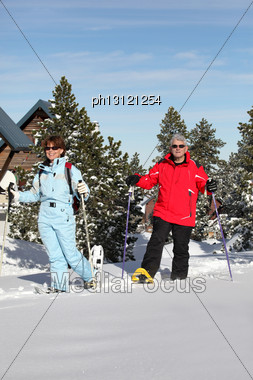 Mature Couple Walking In Snow Shoes Stock Photo