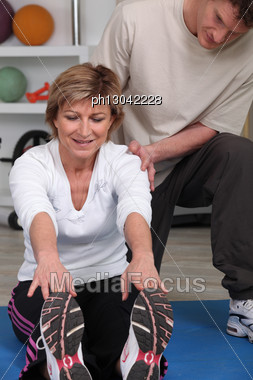 Mature Woman Doing Exercise Helped By Physiotherapist Stock Photo