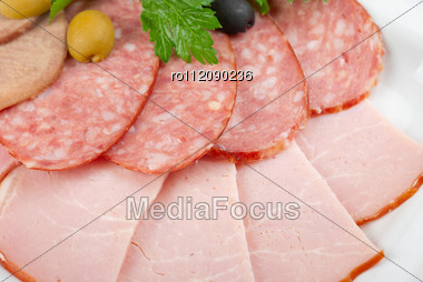 Meat Assortment Of Beef Tongue, Sausage, Meat And Ham With Greens Stock Photo