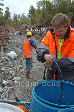 Men Collect In Microphone Cables Used For Seismic Test, Westland, New Zealand Stock Photo