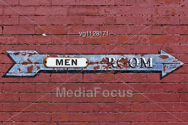Men Room Arrow Directional Weathered Sign Over Red Brick Wall Stock Photo
