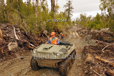 Men Travel In An All Terrain Vehicle While Setting Out Cables For A Seismic Reflective Survey On The West Coast Of New Zealand Stock Photo