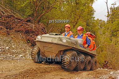 Men Travel In An All Terrain Vehicle While Working On The West Coast Of New Zealand Stock Photo