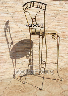 Metal Chair At Sun Light. Chair On Old Stone Background. Retro Chair Casts Shadow Stock Photo
