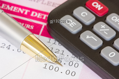 Metal Pen, Calculator And Payslip With Monthly Wage Stock Photo
