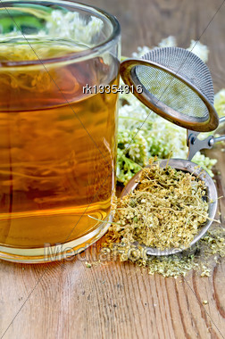 Metal Sieve With Dried Flowers Of Meadowsweet, A Bouquet Of Fresh Flowers Of Meadowsweet, Tea In Glass Mug On A Background Of Wooden Boards Stock Photo