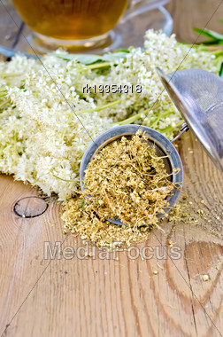 Metal Sieve With Dried Flowers Of Meadowsweet, A Bouquet Of Fresh Flowers Of Meadowsweet, Tea In A Glass Cup On A Background Of Wooden Boards Stock Photo