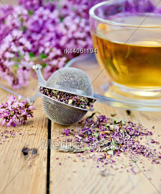Metal Sieve With Dried Flowers Of Oregano, A Herbal Tea In A Glass Cup, Fresh Flowers Of Oregano On The Background Of Wooden Boards Stock Photo