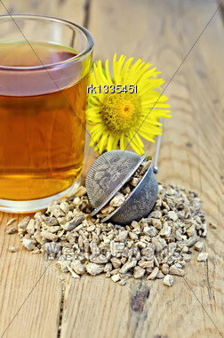 Metal Sieve With Elecampane Root, Fresh Yellow Flower Elecampane, Tea In Glass Mug On A Background Of Wooden Boards Stock Photo