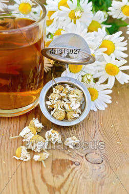 Metal Strainer With Dried Chamomile, A Bouquet Of Fresh Flowers Chamomile, Tea In Glass Mug On A Background Of Wooden Boards Stock Photo