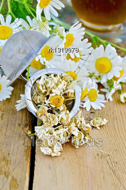 Metal Strainer With Dried Chamomile, A Bouquet Of Fresh Flowers Chamomile, Tea In A Glass Cup On A Background Of Wooden Boards Stock Photo