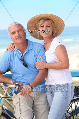 Middle-aged Couple Enjoying Bike Ride By The Sea Stock Photo