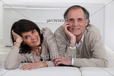Middle-aged Couple Lying On A Futon Stock Photo