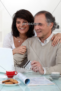 Middle-aged Couple Sat At Computer With Credit-card Stock Photo