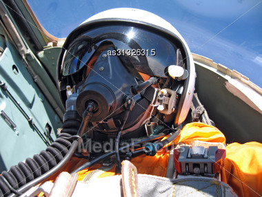 Military Pilot In The Plane In A Helmet In Dark Blue Overalls Against The Blue Sky Stock Photo
