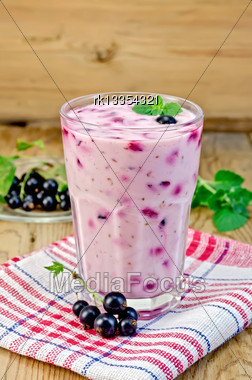 Milk Cocktail With Black Currant And Mint In A Glass On A Napkin, A Saucer With Currant Berries On A Background Of Wooden Boards Stock Photo