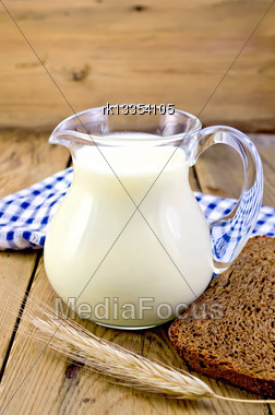 Milk In A Glass Jar With Rye Bread, A Blue Checkered Napkin, Rye Spikelet On The Background Of Wooden Boards Stock Photo