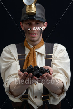 Miner Dressed In 19th Century Clothes Holds A Handful Of Coal - The Energy Behind The Industrial Revolution Stock Photo