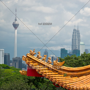 Mixture Of Architectural Styles In Kuala Lumpur, Malaysia. The Roof Of Ancient Chinese Temple On The Background Of Two Symbols Of Kuala Lumpur - KL Tower And Petronas Twin Towers. Stock Photo